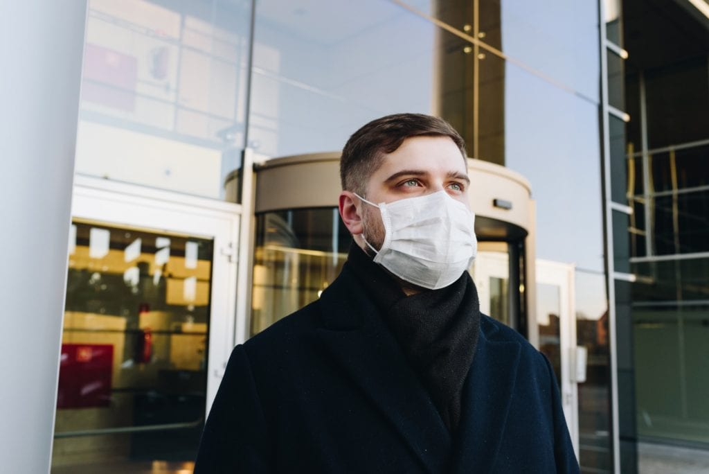 man walking out of apartment building with a surgical mask on for coronavirus