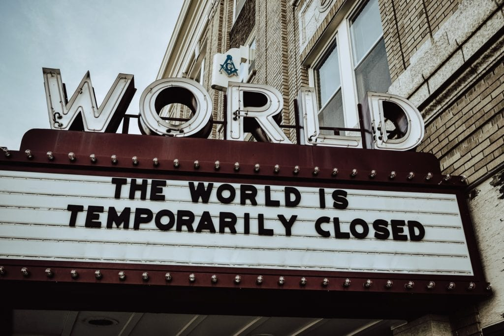 red and white theater with marquee that says the world is temporarily closed