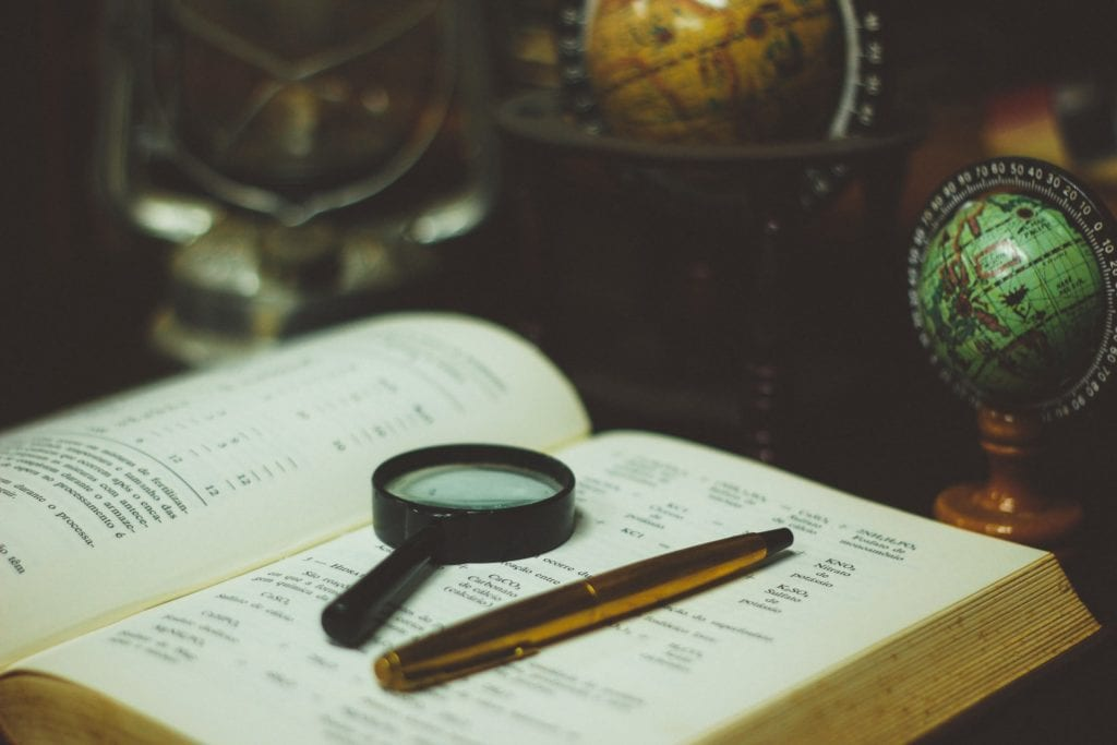 magnifying glass on book inspection analysis