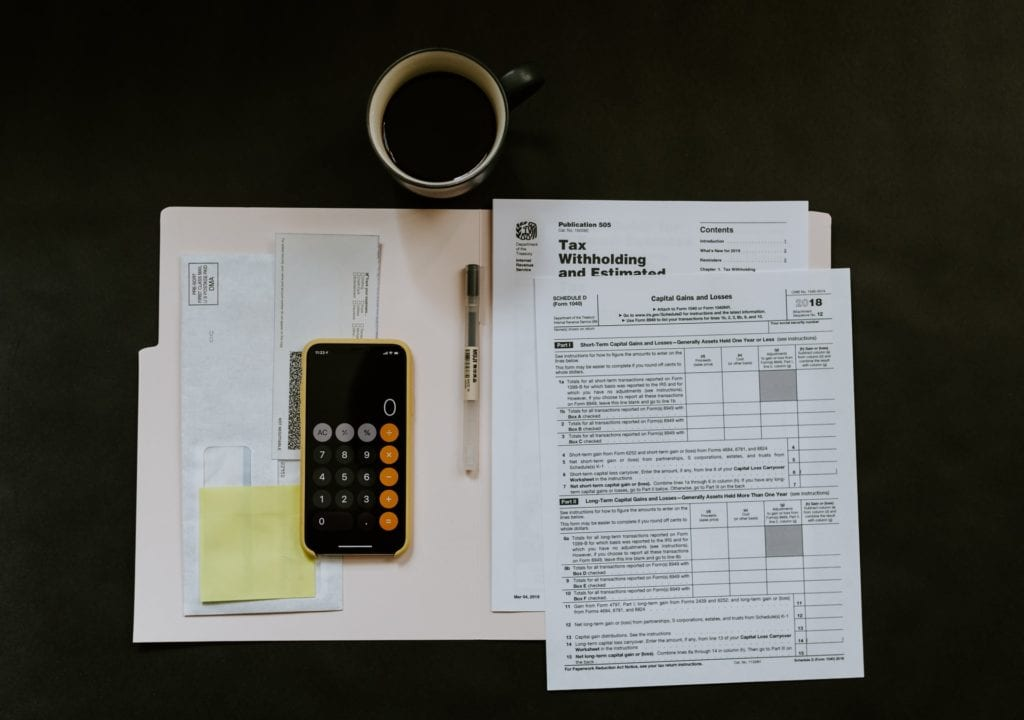 papers on desk with phone calculator and pen for determining finance for home loans