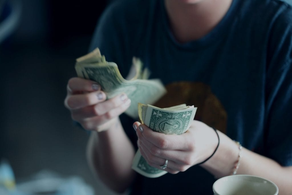 woman counting bank notes to pay her bills