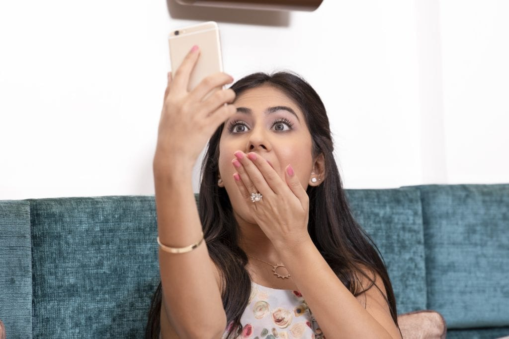 young south asian woman taking a facetime of herself on a couch for a real estate showing